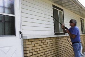 14899814 - home owner pressure washing the siding of his house