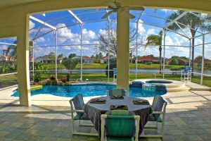 65966501 - a view from a lanai of a pool, spa and lake.